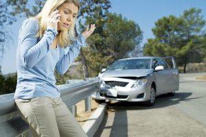 девушка с телефоном возле разбитой машины